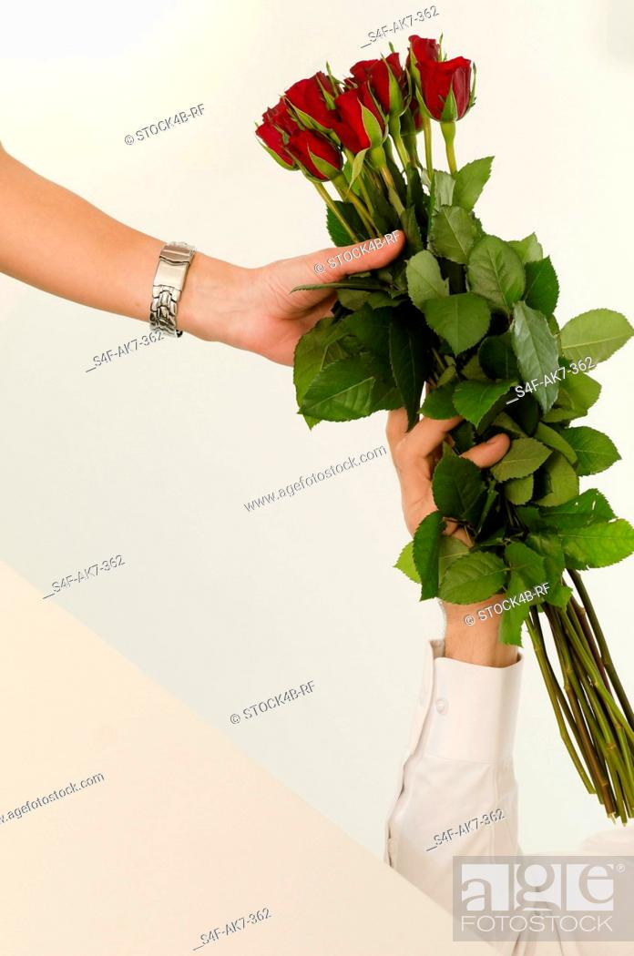 Stock Photo: Man giving woman bunch of red roses.