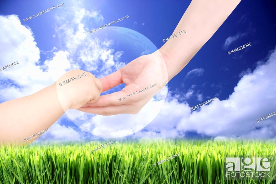 Stock Photo: Lohas, Environmental Conservation, Digitally generated image of human hand holding baby's hand with grass and blue sky in background.