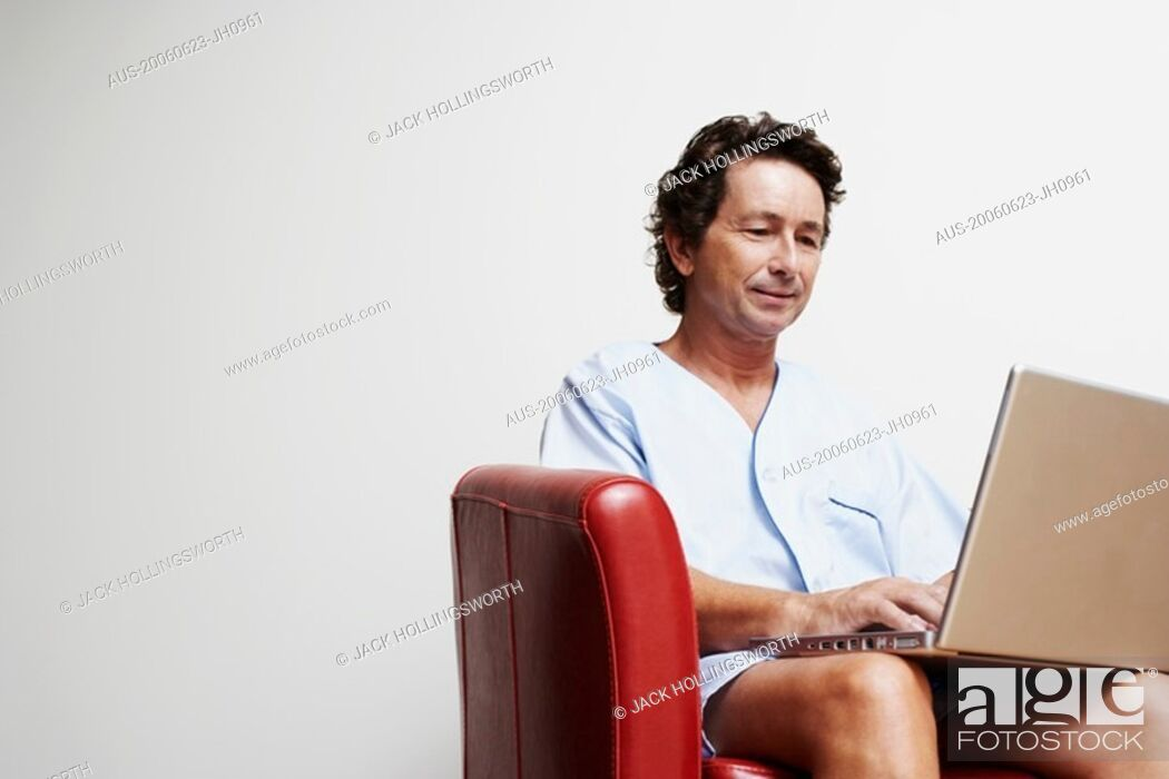Stock Photo: Mature man sitting in an armchair and using a laptop.