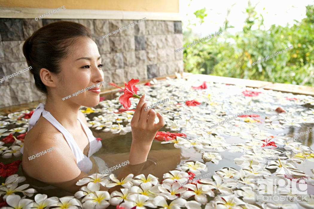 Stock Photo: Woman in pool with flower petals.