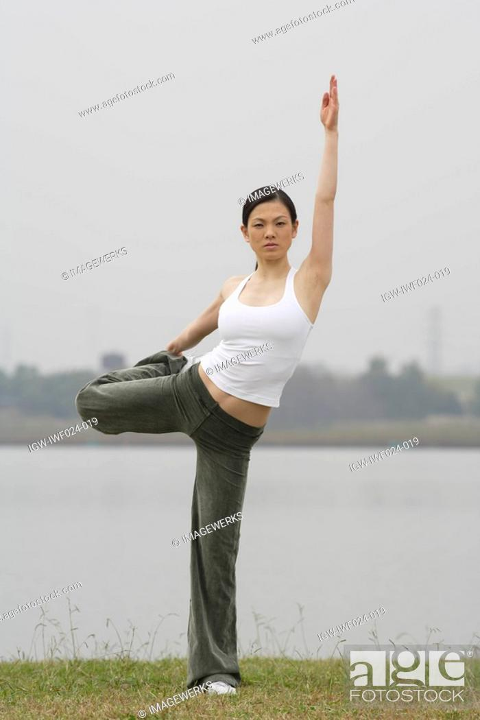 Stock Photo: View of a young woman balancing on one leg.