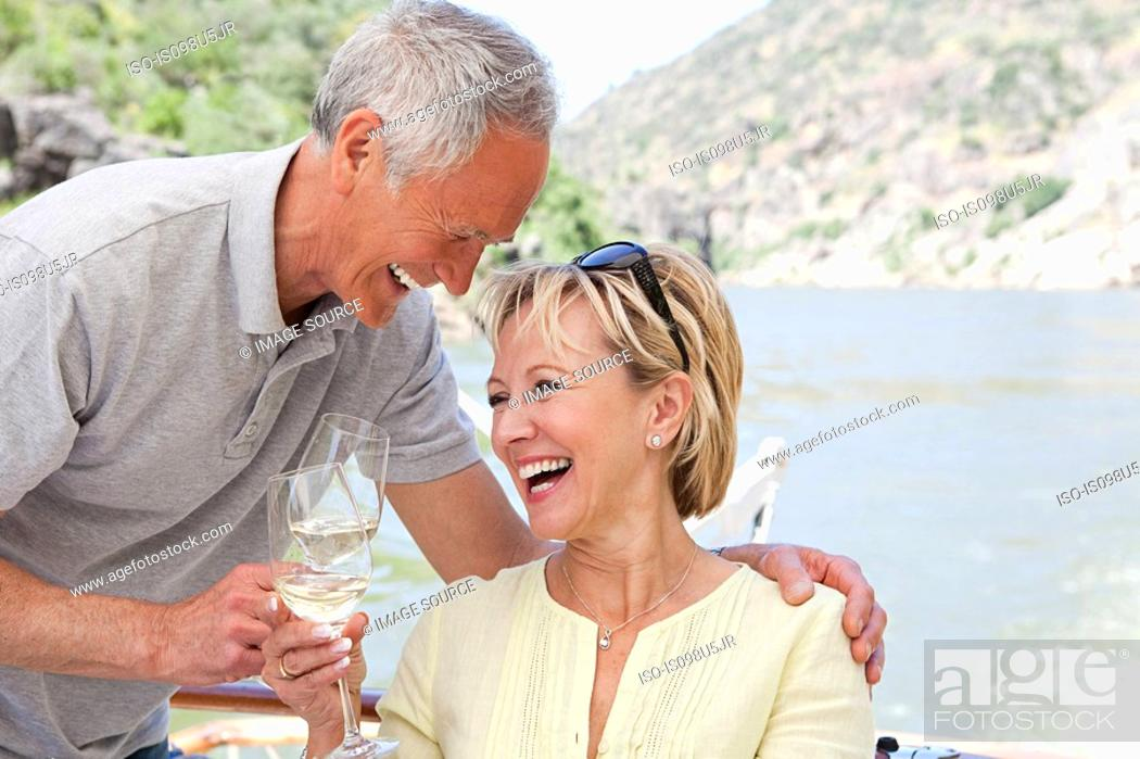 Stock Photo: Senior couple with glasses of wine on a boat holiday.