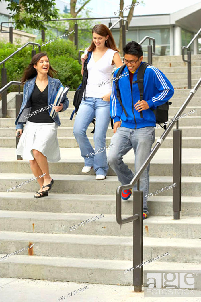 Stock Photo: Three college students moving down a staircase.