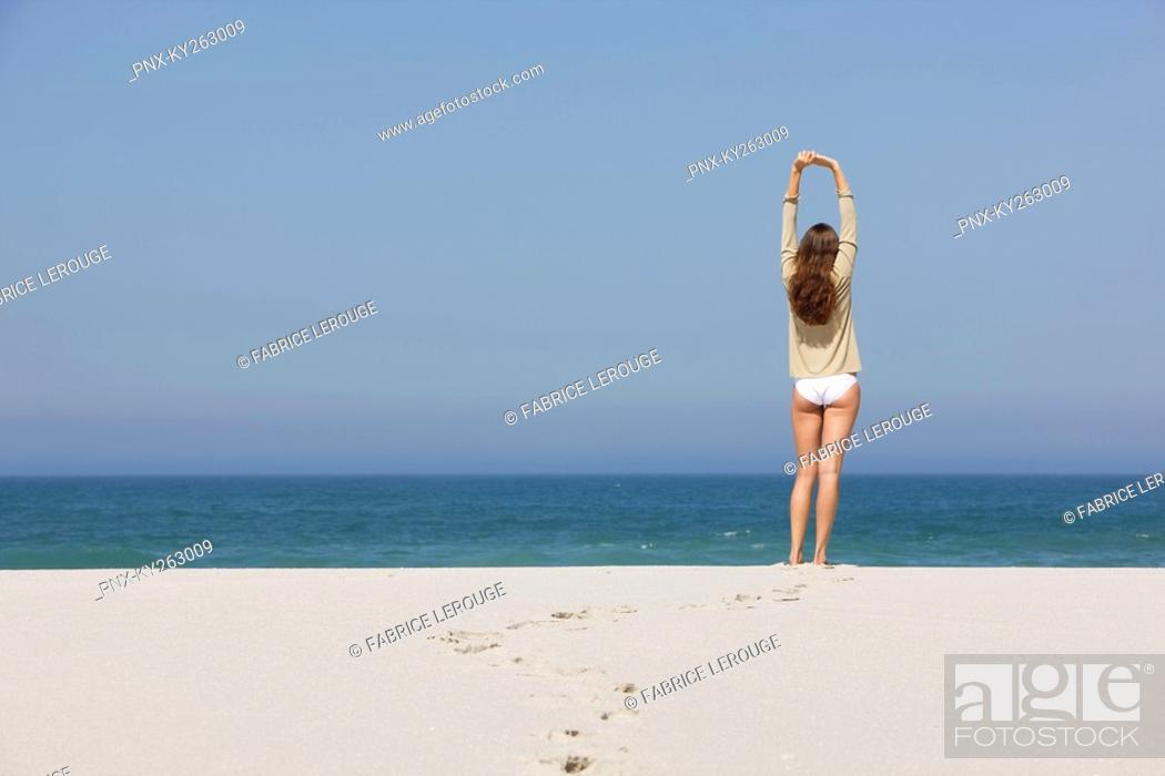 Stock Photo: Rear view of a woman standing on the beach with her arms raised.