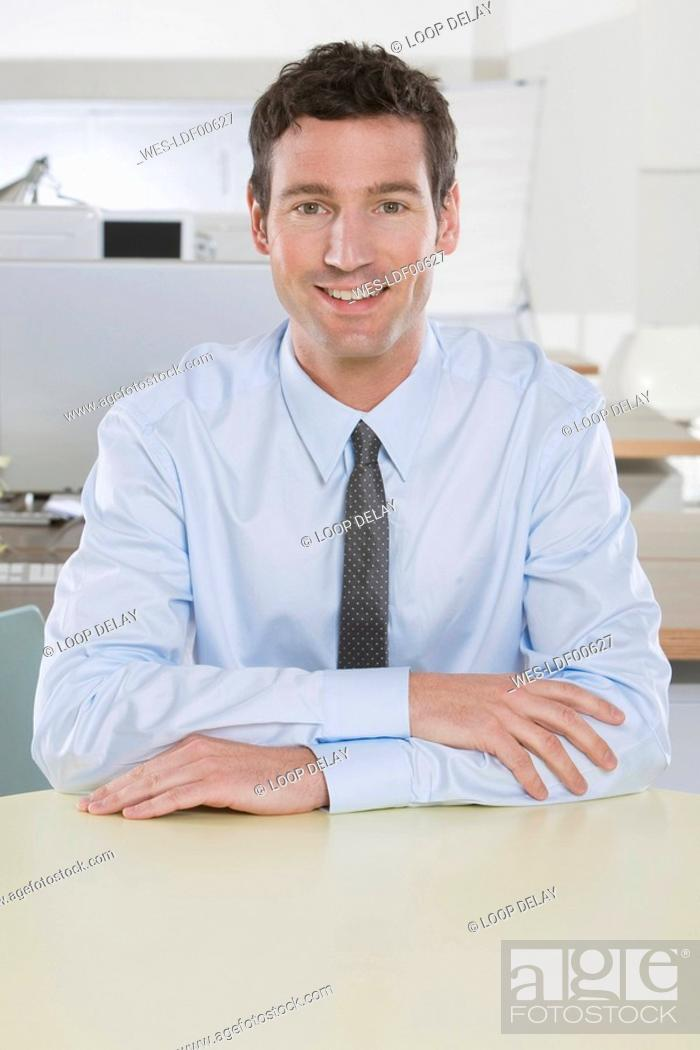 Stock Photo: Germany, Munich, business man in office, smiling, portrait.
