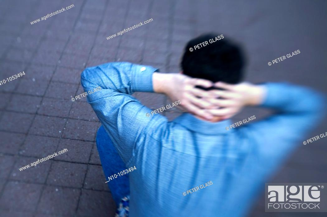 Stock Photo: Young man sitting on a sidewalk.