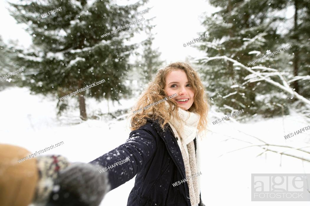 Stock Photo: Portrait of happy young woman holding hand in winter forest.
