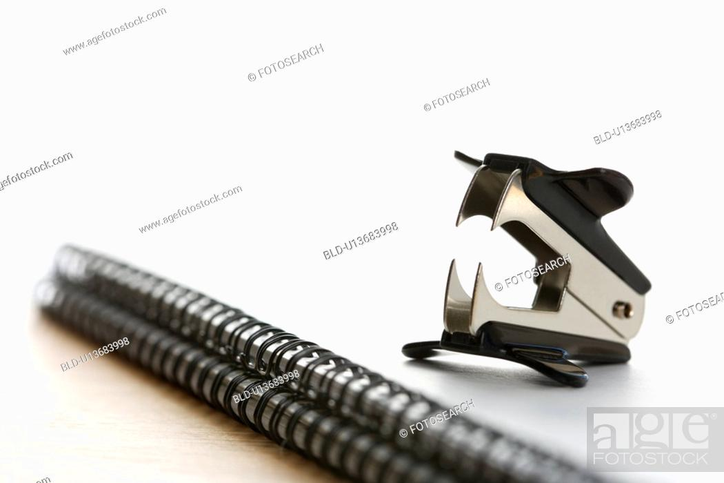 Stock Photo: Black staple remover on top of a spiral bound notebook.