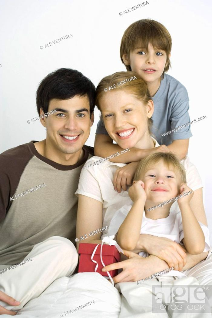 Stock Photo: Family sitting together, smiling at camera, mother holding gift.