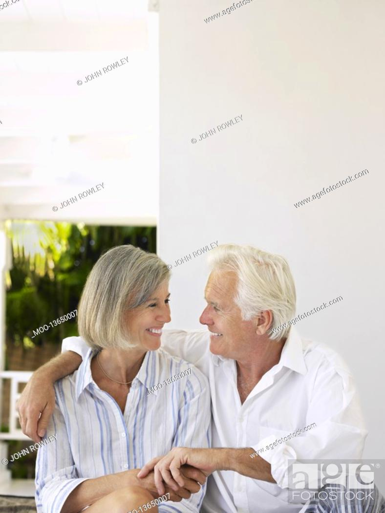Stock Photo: Senior couple sitting on verandah looking in eyes and smiling.