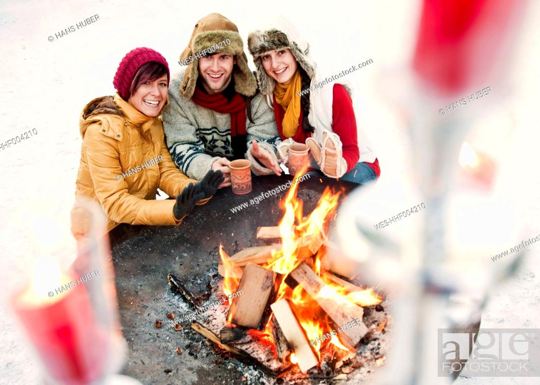 Stock Photo: Austria, Salzburg, Man and women by fire at christmas market, smiling.