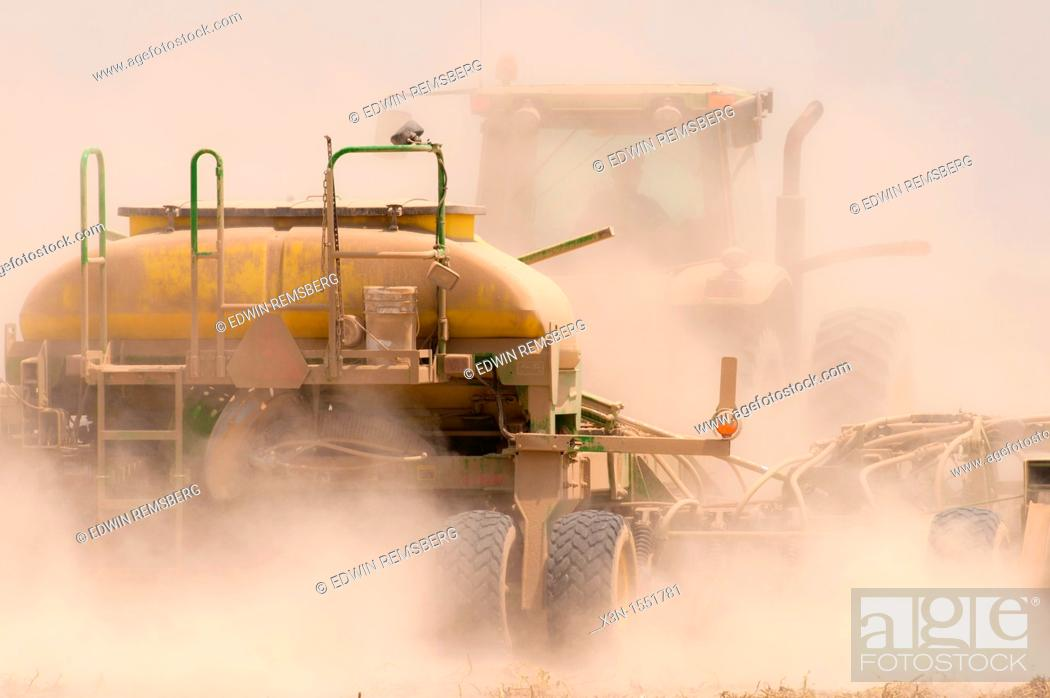 Stock Photo: Tractor in cloud of dust while performing chemical application on dusty field on farm near Hurlock, Maryland.