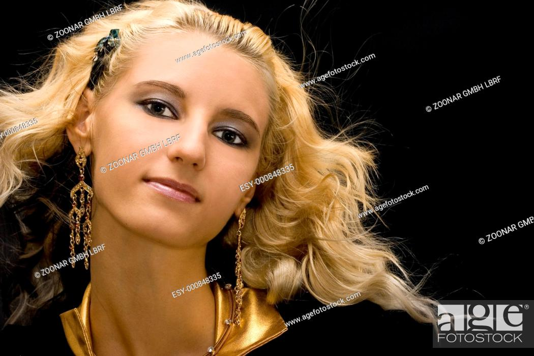 Stock Photo: Portrait of young beautiful blond girl on black background.
