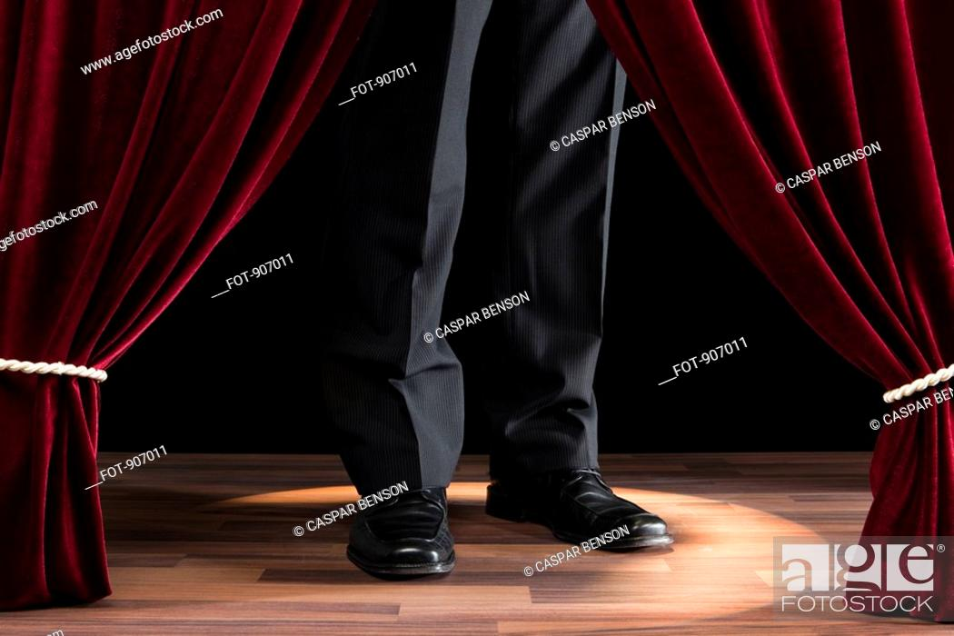 Stock Photo: A Man Standing On A Miniature Theatre Stage.