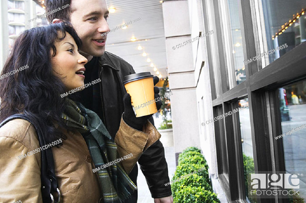 Stock Photo: Couple drinking coffee and window shopping.