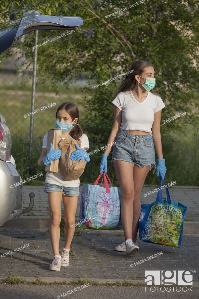 Stock Photo: people wearing mask and gloves coming home from supermarket.