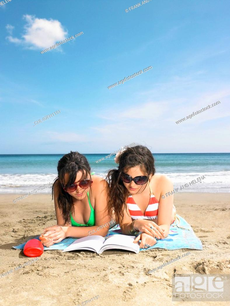 Stock Photo: Two young woman sharing a book.