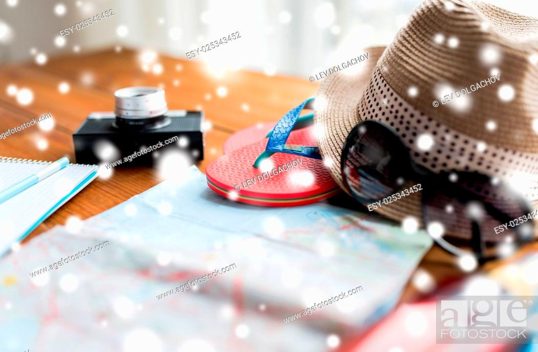 Stock Photo: vacation, tourism and objects concept - close up of travel map, flip-flops, hat and camera on wooden table at home.