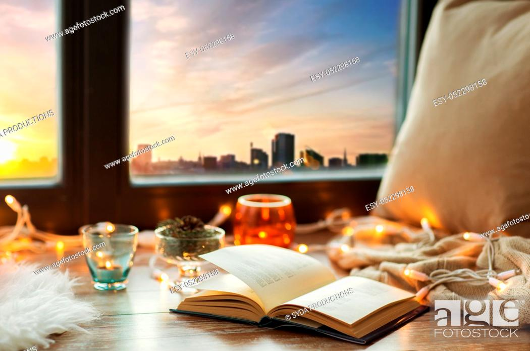 Stock Photo: book, garland lights and candles on window sill.