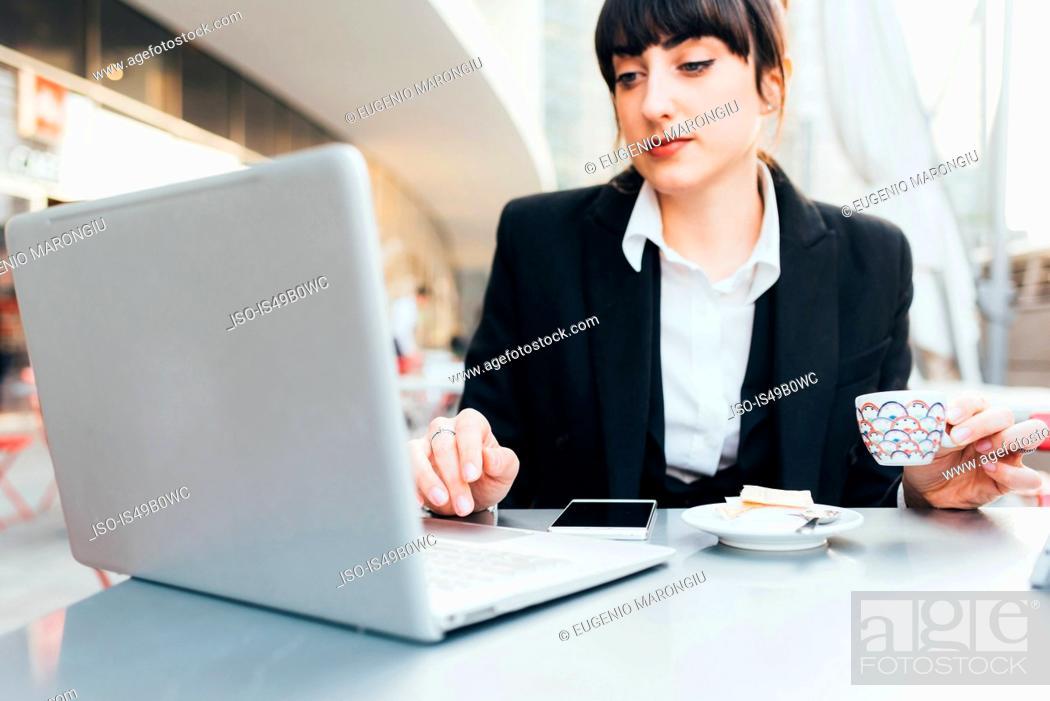 Stock Photo: Businesswoman using laptop in coffee shop, Milan, Italy.