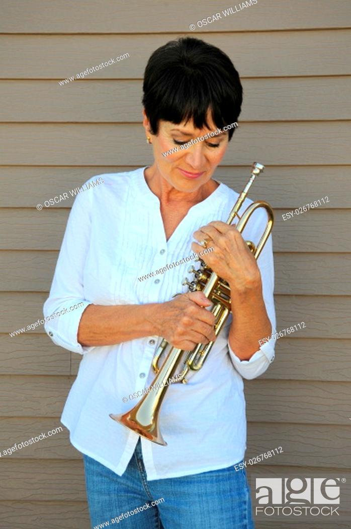 Stock Photo: Mature female beauty holding her trumpet outside.