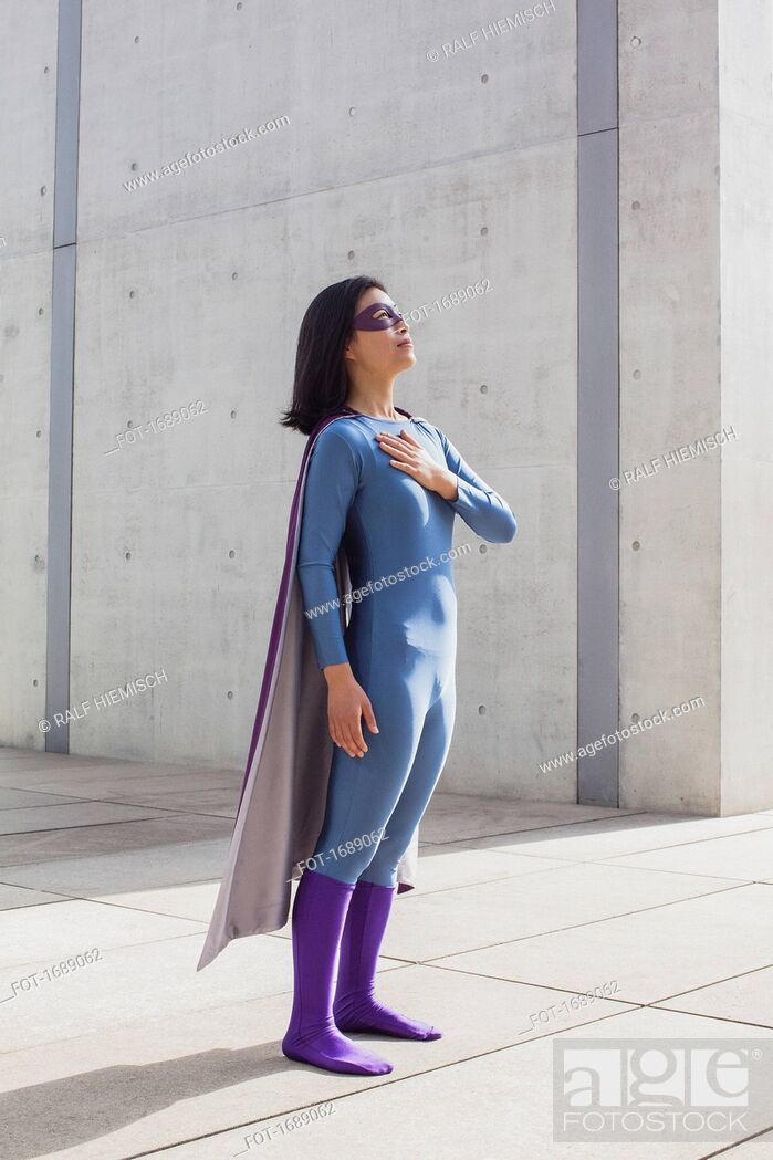 Stock Photo: Confident woman wearing superhero costume standing on floor by wall.