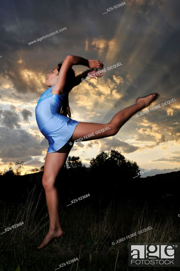 Stock Photo: young gymnast jumping in a meadow at dusk.