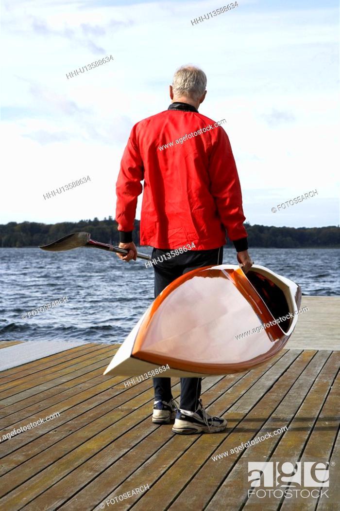Stock Photo: Senior man holding a kayak.