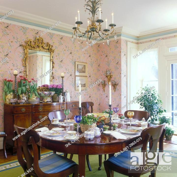 Stock Photo Dining Room Traditional Greek Revival Formal Table Set Pink Print Wallpaper White Trimwork Antique Furniture Gold Gilded Mirror