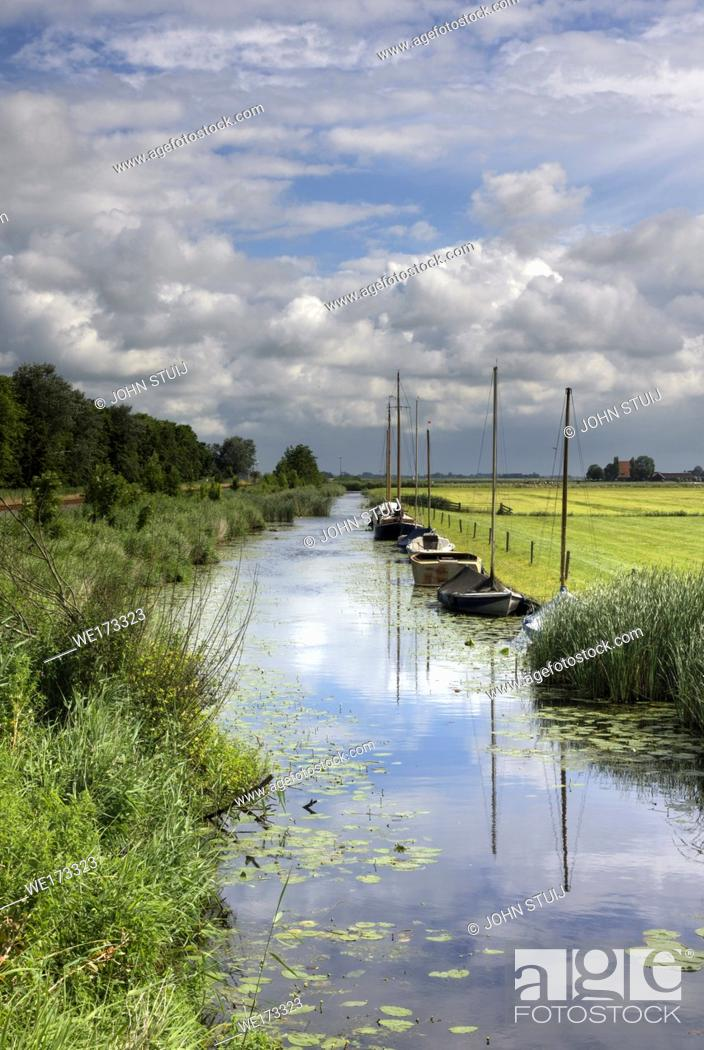 Stock Photo: Moored sailing boats in a canal near the town of Workum in the Dutch province Friesland.