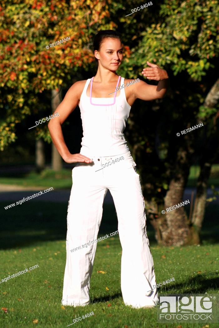 Young woman in an autumnal park practising Qi Gong