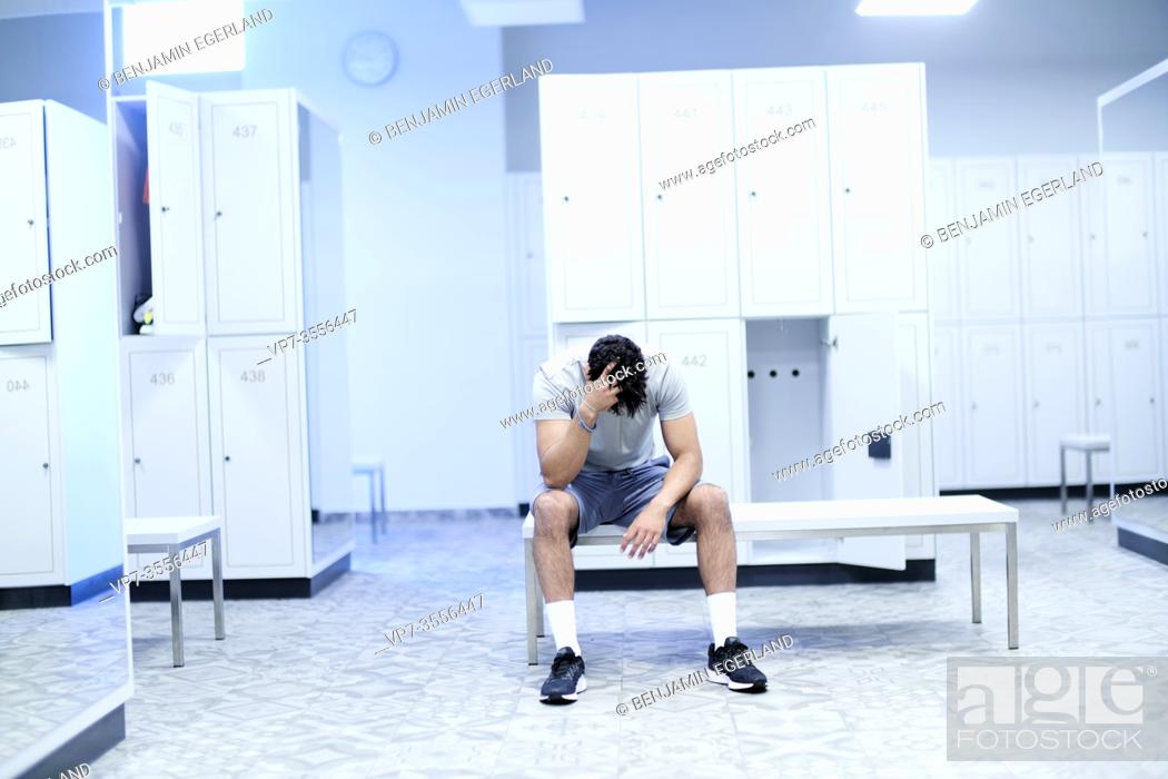 Photo de stock: Tired man sitting in gym locker room.