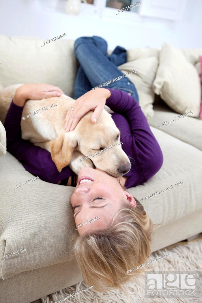 Stock Photo: Young woman playing with her dog on the sofa.