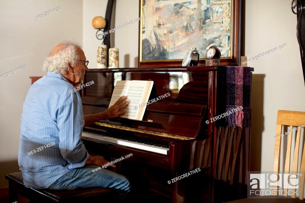 Imagen: Senior man playing piano at retirement home.