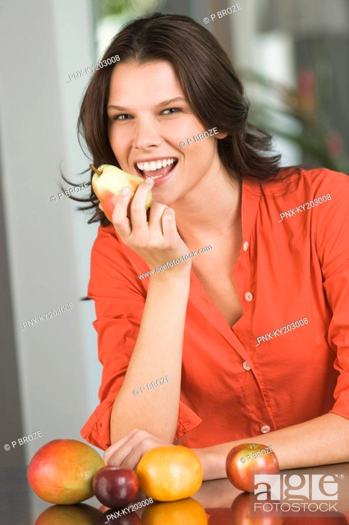 Stock Photo: Woman eating a pear and smiling.