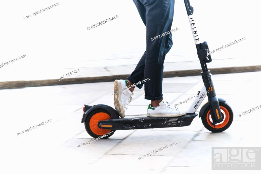 Stock Photo: Italy, Lombardy, Milan, Woman Riding Electric Scooter. . . .