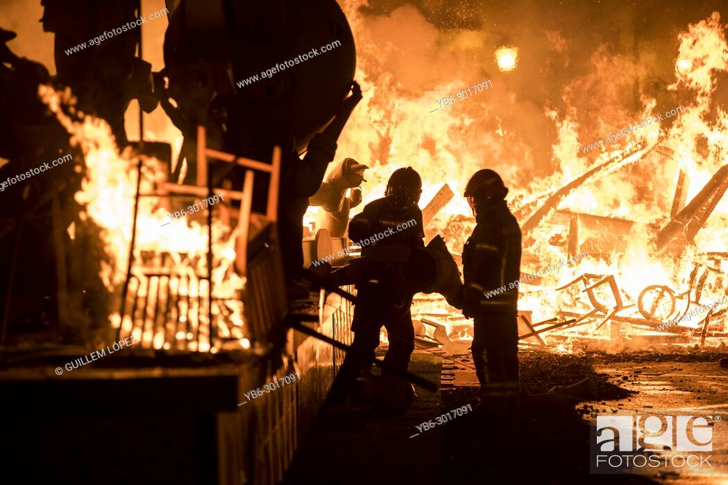 """Stock Photo: Firefighters at work during the night of """"""""La Crema"""""""" the burning at the Valencian town hall square as part of the last day of las Fallas festival in Spain."""