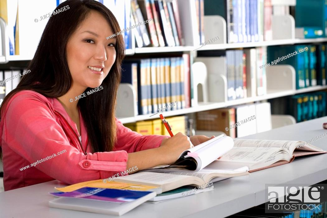 Stock Photo: Woman studying in library, smiling, portrait, close-up.