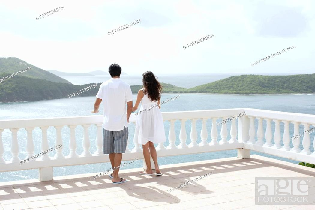 Stock Photo: Young couple looking at ocean on balcony, St. John, US Virgin Islands, USA.