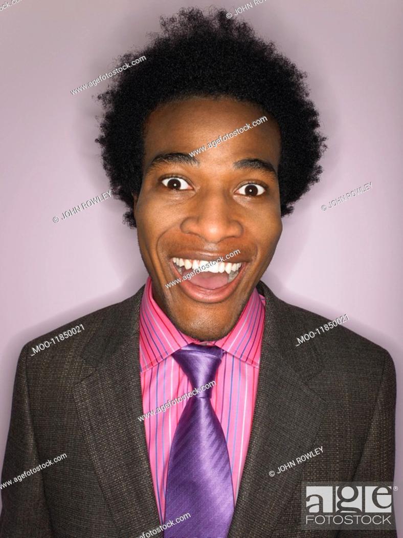 Stock Photo: Man in suit smiling head and shoulders in studio.