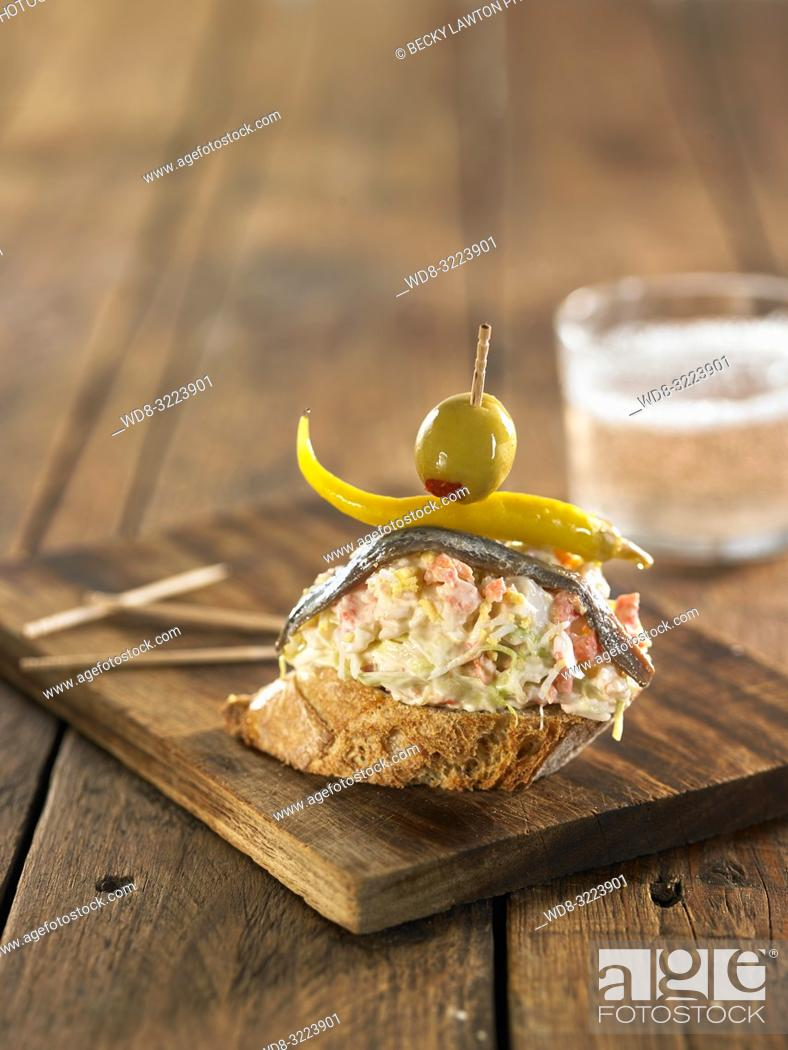 Stock Photo: tostada con ensaladilla rusa, pimiento y oliva y vaso de cerveza / toast with Russian salad, pepper and olive and glass of beer.