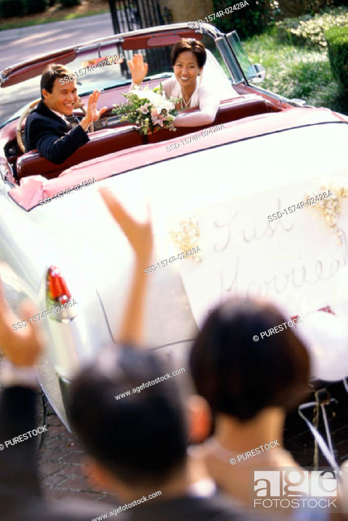 Stock Photo: High angle view of a newlywed couple waving from a convertible car.