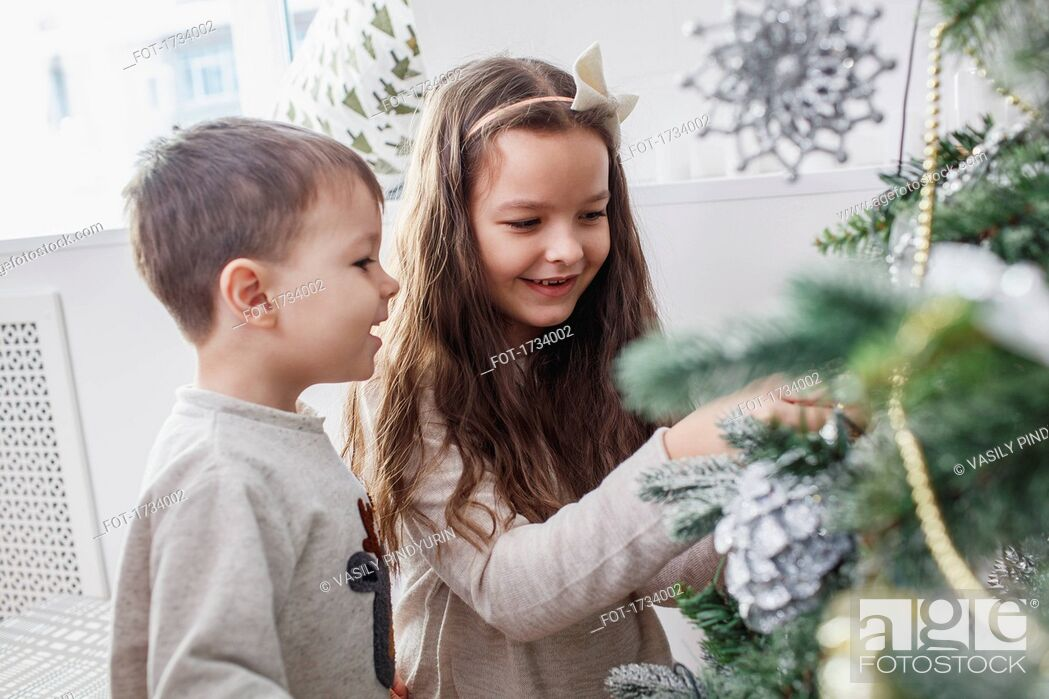 Stock Photo: Happy siblings decorating Christmas tree at home.