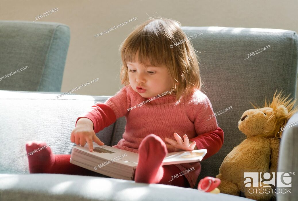 Stock Photo: 18 months old baby girl looking and pointing at inside a book.