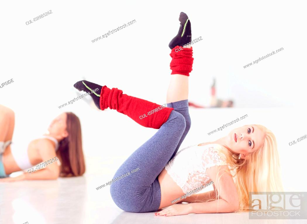 Stock Photo: Portrait of young female ballet dancer leaning back with legs raised.