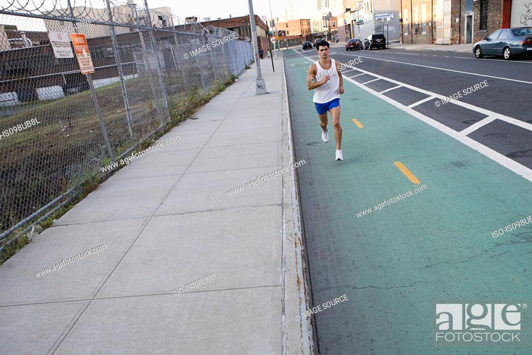 Stock Photo: Male runner on urban street.