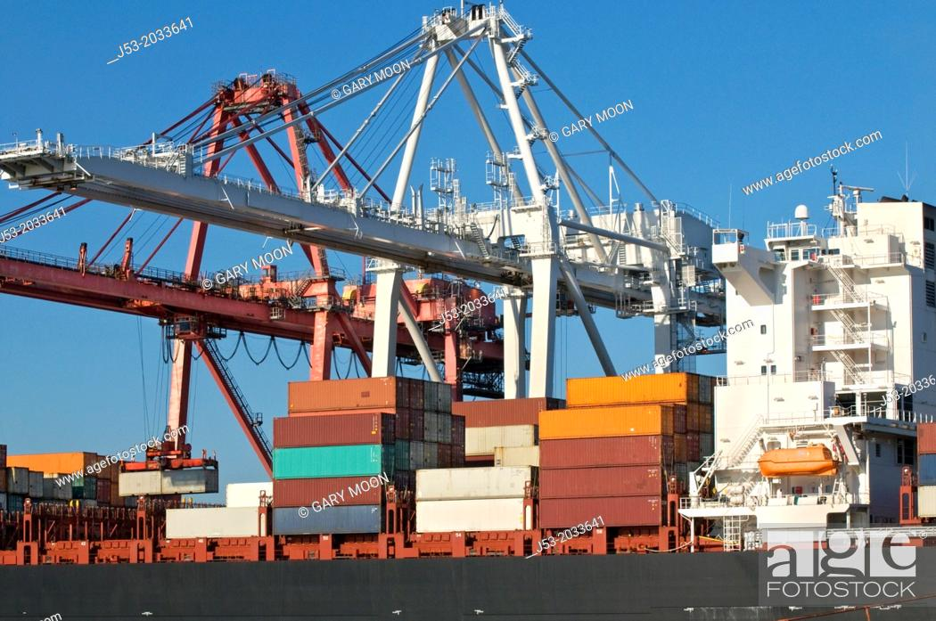 Stock Photo: Container cranes transferrng cargo from container ship at Port of Seattle, Seattle Washington USA.