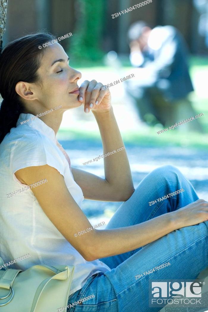 Stock Photo: Woman sitting on ground, leaning back, eyes closed.