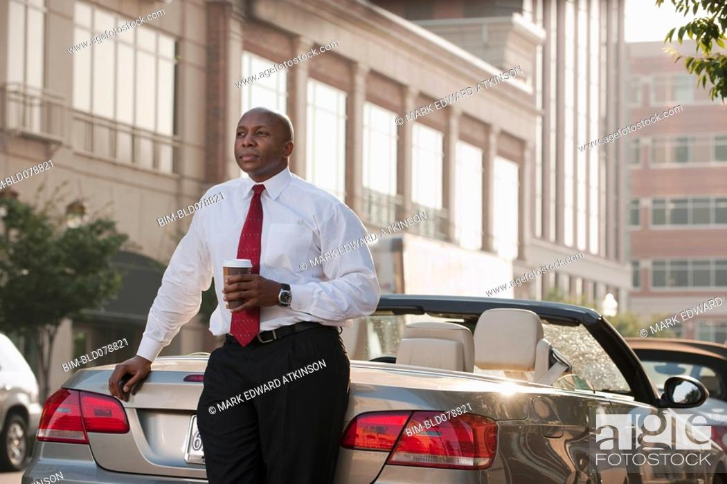Stock Photo: Black businessman drinking coffee near convertible.