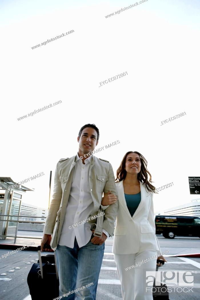 Stock Photo: Young couple arriving at airport with luggage.